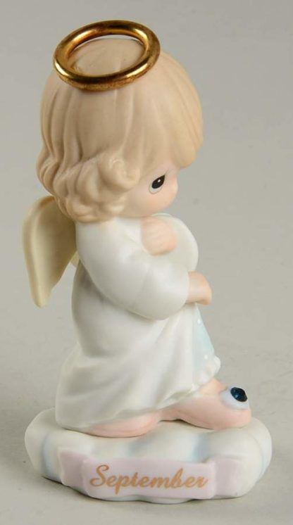 This porcelain figurine depicts an angel with a gold halo and birthstone (sapphire rhinestone).