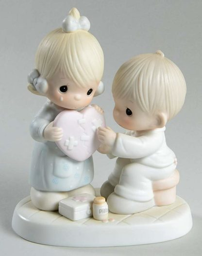 Precious Moments figurine depicts a girl and boy with a bandaged heart.