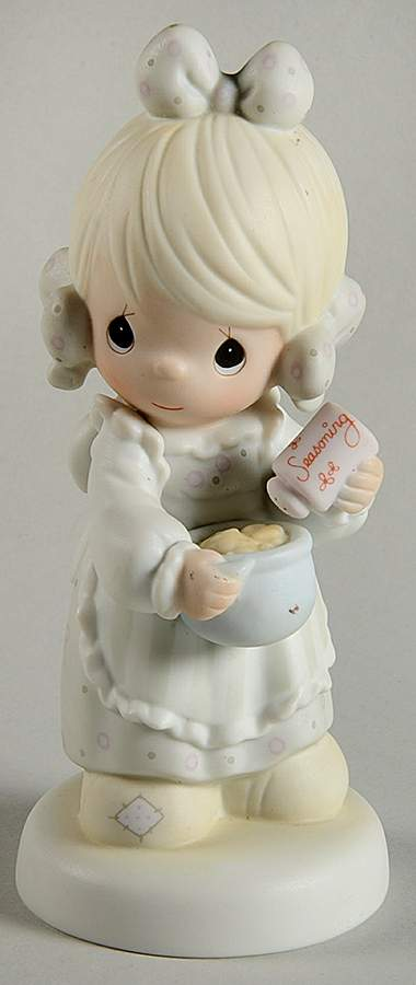 Precious Moments figurine depicts a girl sprinkling seasoning in a mixing bowl.