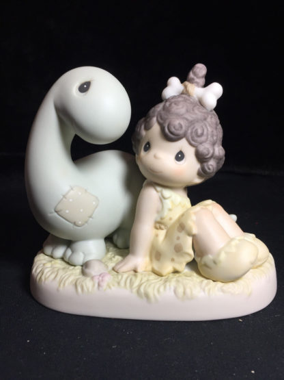 Precious Moments figurine depicts a cave girl with a dinosaur.
