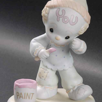 Precious Moments figurine depicts a clown painting his forehead.