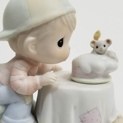 Precious Moments figurine depicts a boy blowing out a candle on a cake - held by mouse.