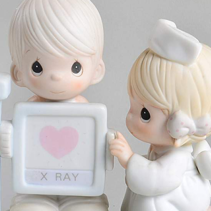 Precious Moments figurine depicts a nurse x-raying a patient.