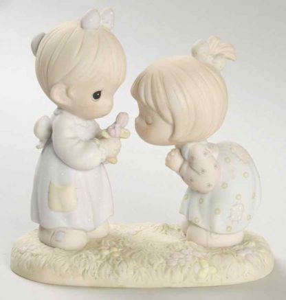 Precious Moments figurine depicts two girls smelling a flower.