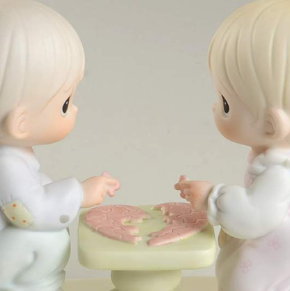 Precious Moments figurine depicts a boy and girl putting a puzzle together at a table.