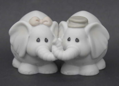 Porcelain figurine depicting boy and girl elephants with trunks entwined