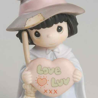 """Precious Moments figurine depicts a girl dressed as a witch with broom and a heart with the words """"Love Luv XXX""""."""
