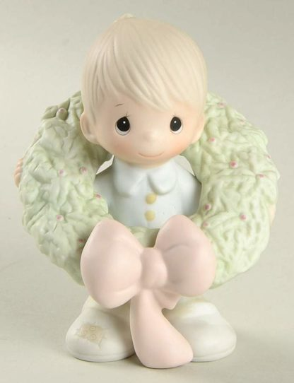 porcelain figurine depicts a boy with a Christmas Wreath around him.