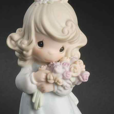 Porcelain figurine from the Growing In Grace series, this piece depicts a girl holding a bouquet of sixteen roses.