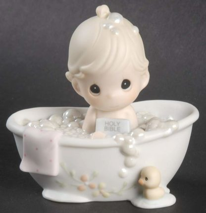 Porcelain figurine of child in bathtub filled with bubbles, holding bible