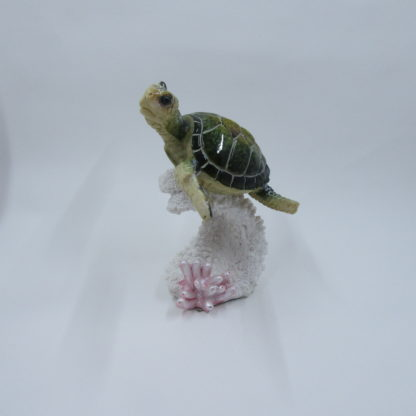 "5"" tall green swimming sea turtle on pink coral."