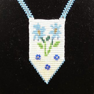 This Handmade Native American authentic necklace features blue flowers on a white panel. Hand stitched with seed beads features an intricate design of two blue flowers, stems and leaves plus more blue blooms below.
